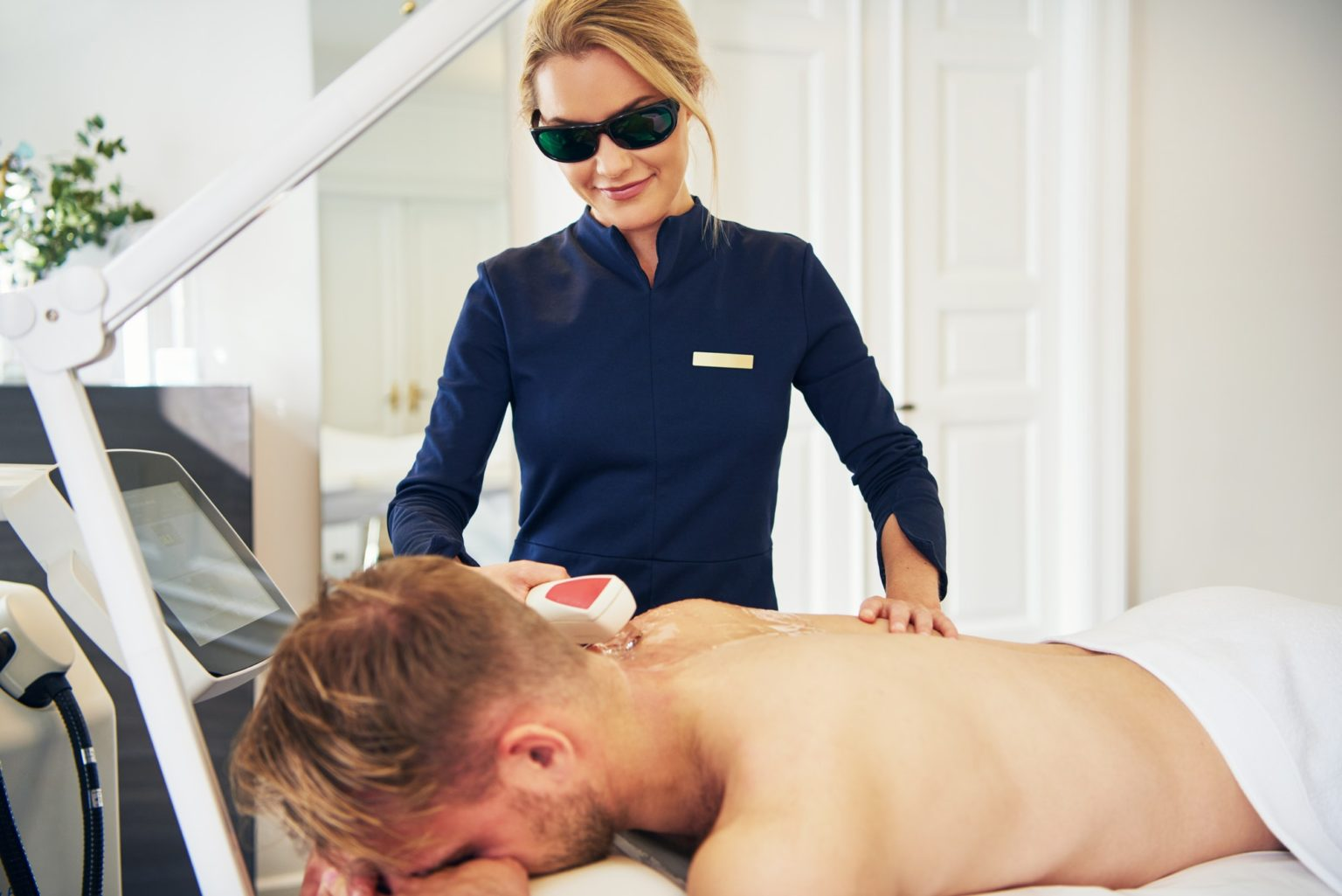 Young beautician performing laser hair removal procedure on a client