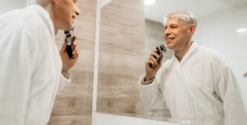 Cheerful adult man shaves at mirror in bathroom