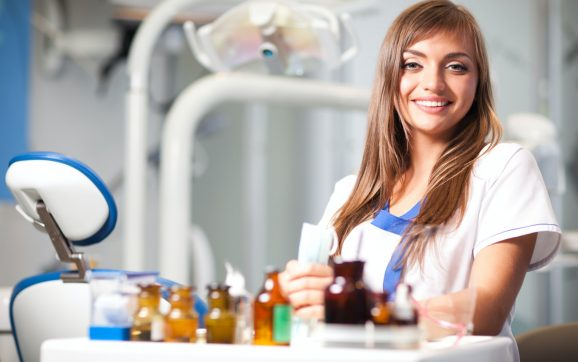 Young nurse woman in white uniform sitting near dental chair in dental office in clinic with