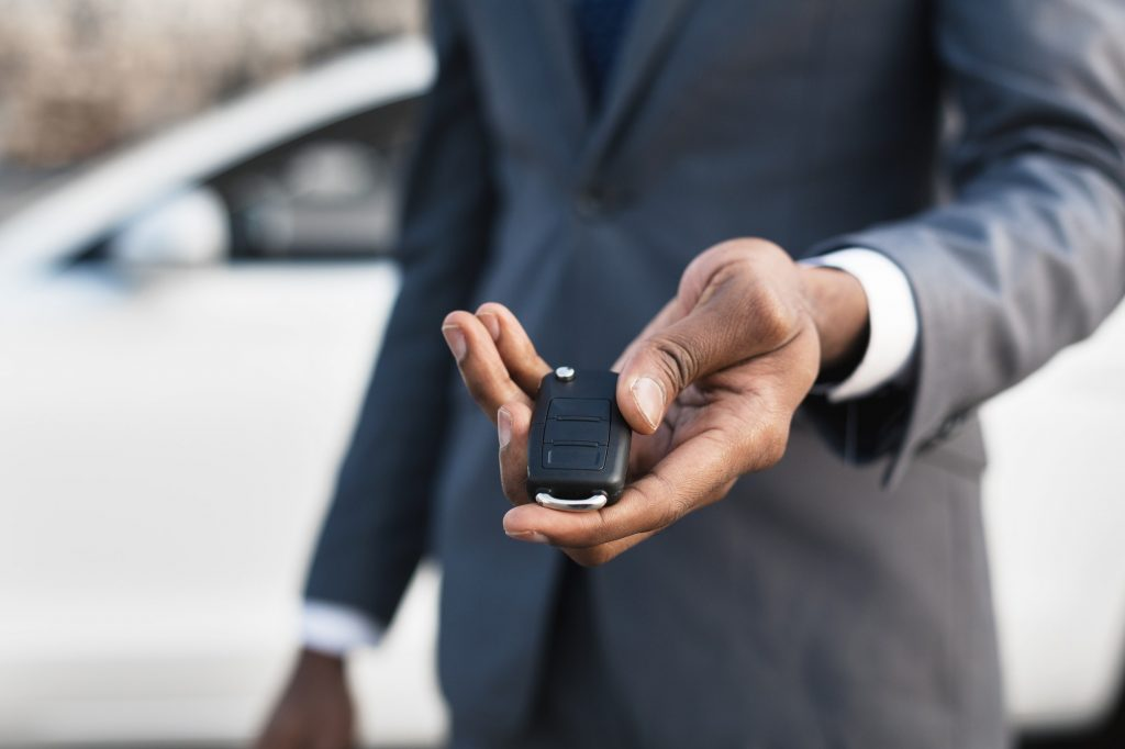 Car sale concept. Man hand giving car key