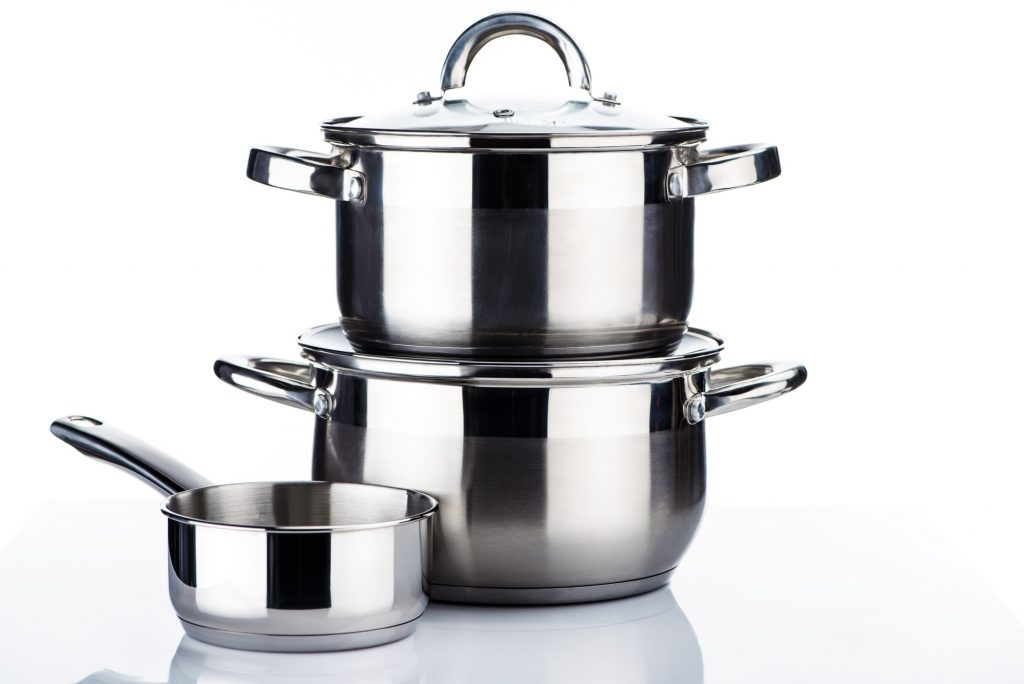 close-up view of shiny stainless steel pots and pans on white