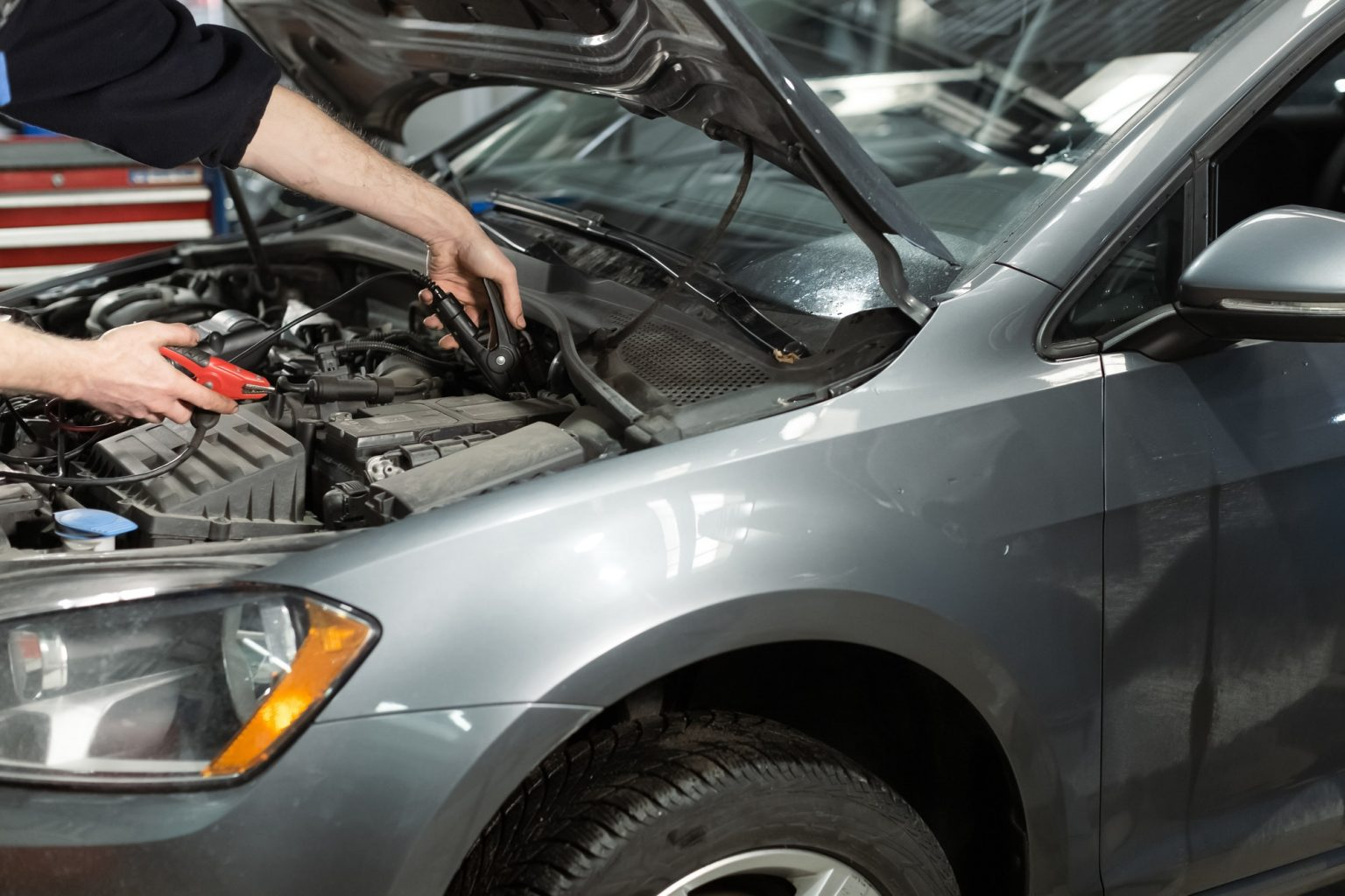 Technician hands measure the voltage of the battery in the car at service station