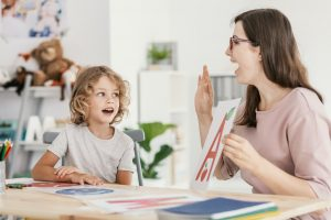 Speech therapist teaching letter pronunciation to a young boy in